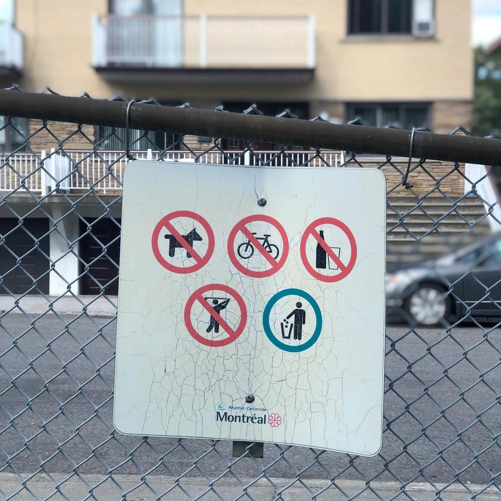 Panneau dans un parc avec l'interdiction d'avoir un chien, un vélo, des boissons (alcoolisées), de faire du hockey (?), un seul pictogramme autoriser: jeter à la poubelle.